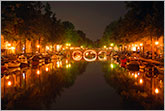 Amsterdam canal and bridge at night with beautiful lights and reflections